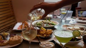wine pouring into glass at large table of food